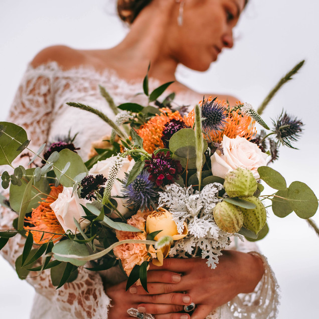 bohemian bride at the beach with a bouquet
