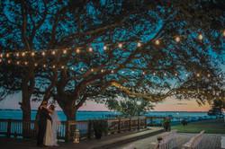 Lightbloom Photography captures Southport Community Building wedding couple under string lights