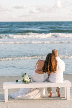 Couple sitting on bench at Oak Island, NC Beach Elopement Photo by KMI Photography