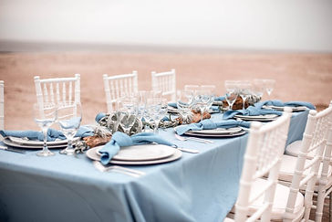 An Oak Island wedding with photography by Hen House Photo. A beautiful Coastal NC wedding tablescape with a driftwood centerpiece, white chiavari chairs and a slate blue beach wedding look. NC wedding planners Kim Sirkin and Teresa Robbin of Blue Satin Bee designed this NC beach wedding.