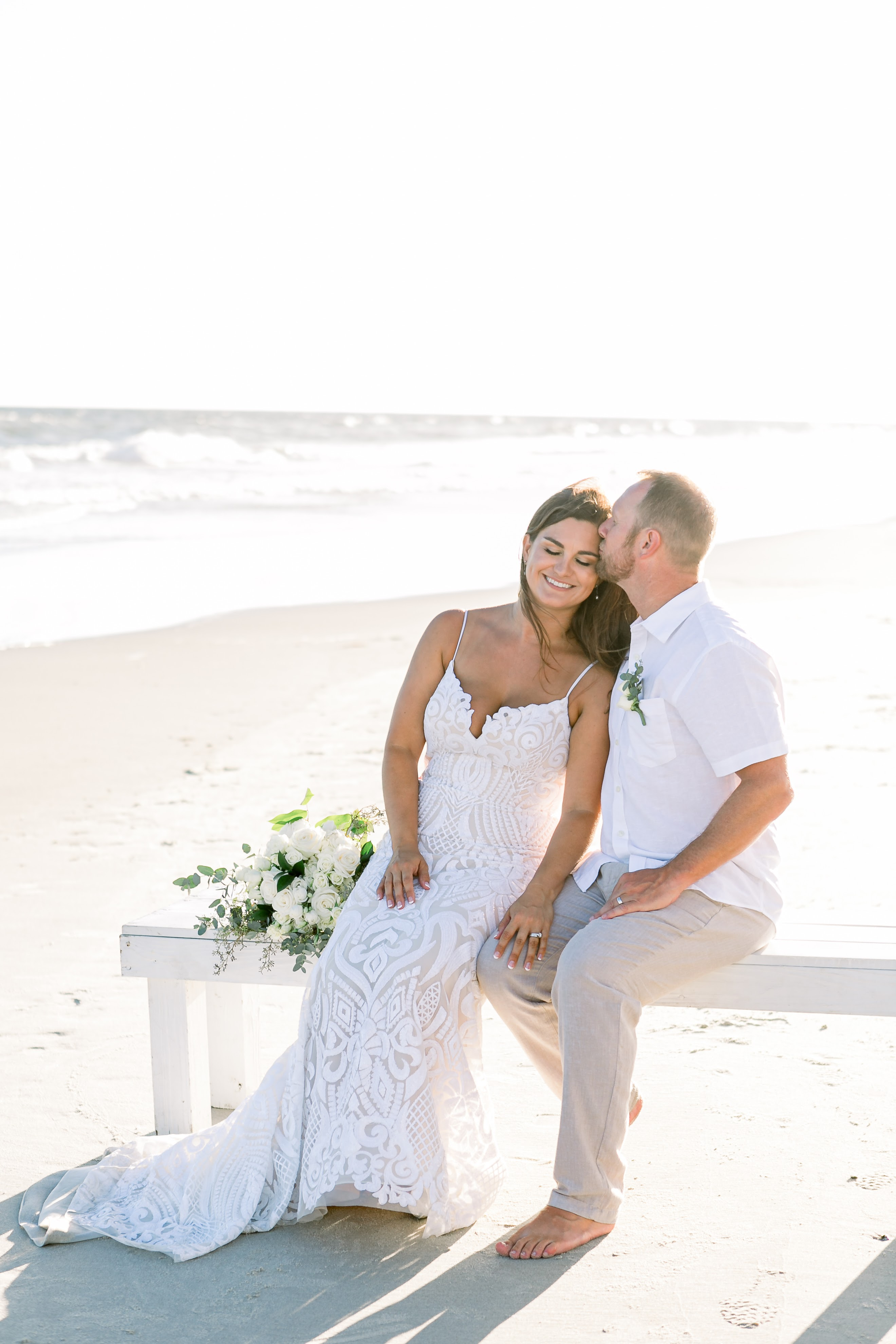 KMI Couple sitting on bench at Oak Island NC Beach Elopement Wedding at the beach
