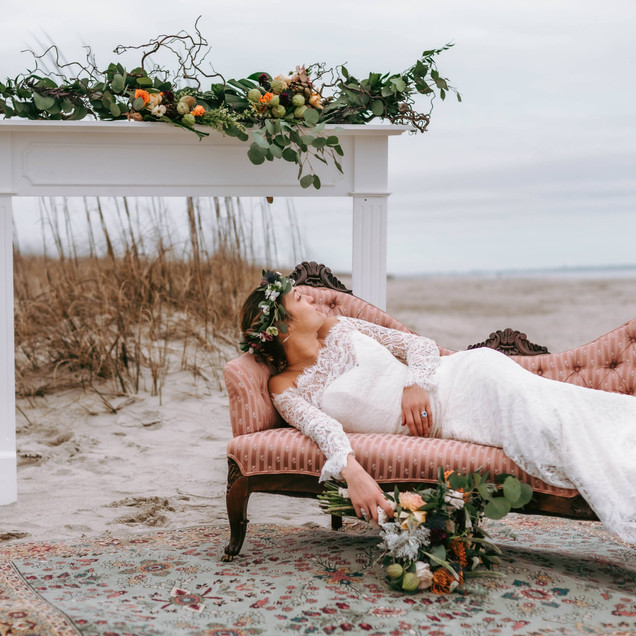 Boho Bride on vintage sofa with mantle in background beach wedding decor Oak Island Blue Satin Bee