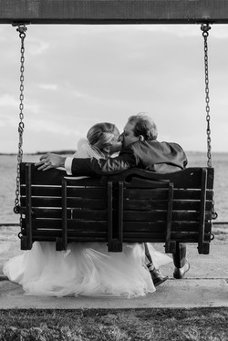 Eliflo Media Bride and Groom on Southport Waterfront Bench Kissing
