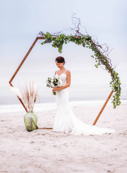Hen House Photo shoots bride  and ceremony arbor at Caswell Beach, NC
