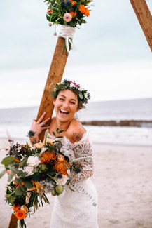 smiling Boho bride in vintage wedding dress with triangle arbor at Oak Island beach wedding Blue Satin Bee
