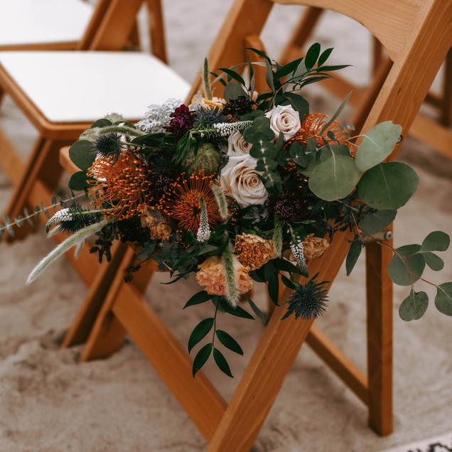 bouquet in natural wood folding chair beach wedding ceremony Oak Island wedding Blue Satin Bee