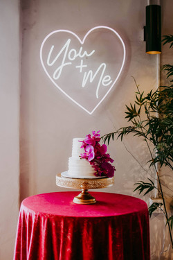 Wedding cake with neon sign at 801 Ocean Oak Island, NC Wedding - Photo by Hen House Photo