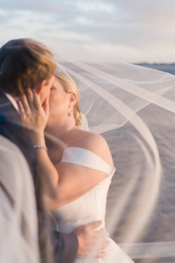 Bride and Groom Kissing after La Polena Southport, NC Wedding Photo by Eliflo Media