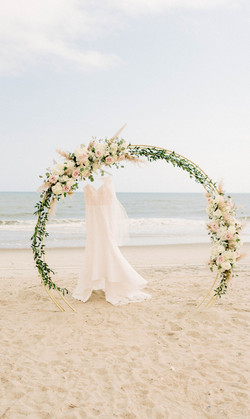 Elopement on Oak Island, NC - Bride's gown hangs from floral arch. Photo by Chelsea Allegra