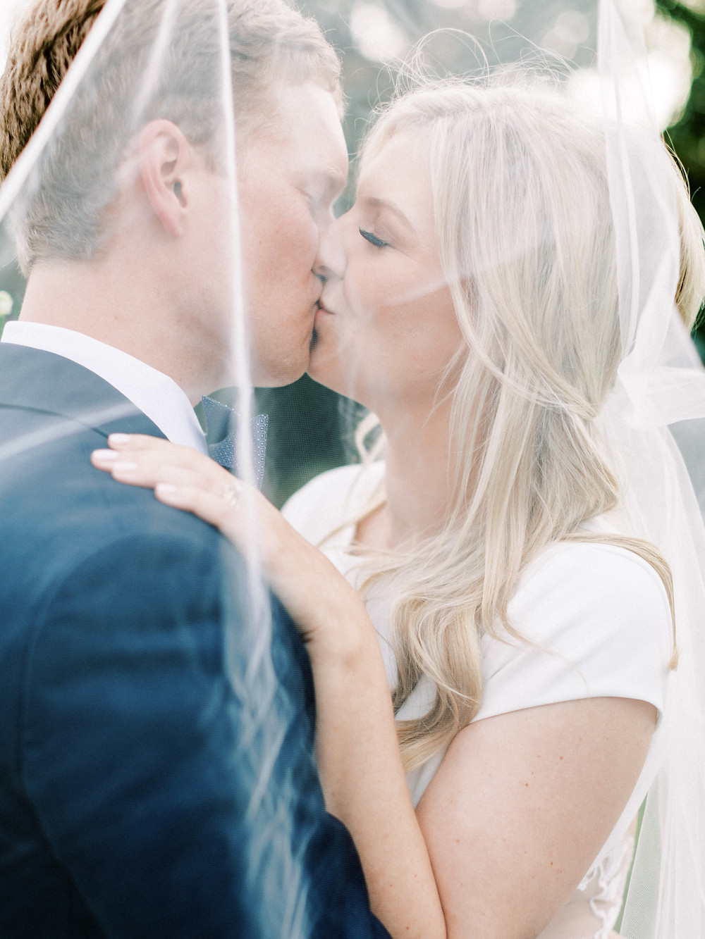 Summer wedding bride and groom kissing behind veil Heather Webster Photography & Blue Satin Bee NC Wedding Planner
