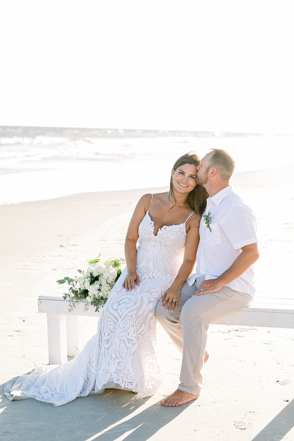 Oak Island Beach Elopement Couple sits on bench together Blue Satin Bee elopement package couple with KMI photography