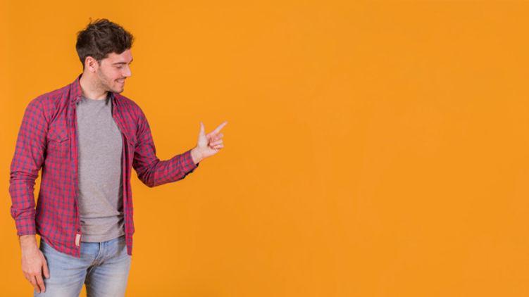 jovem-feliz-apontando-o-dedo-contra-um-f