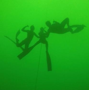 three female freedivers in cenote Yum Kin near Playa del Carmen Mexico holding their breath.