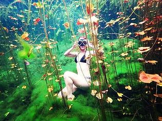 Freediver posing in Nicte-Ha, a cavern full of water lilies offering a different underwater landscape near Tulum
