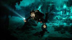 Dive guide entering Dos Ojos cenote between Tulum and Playa del Carmen