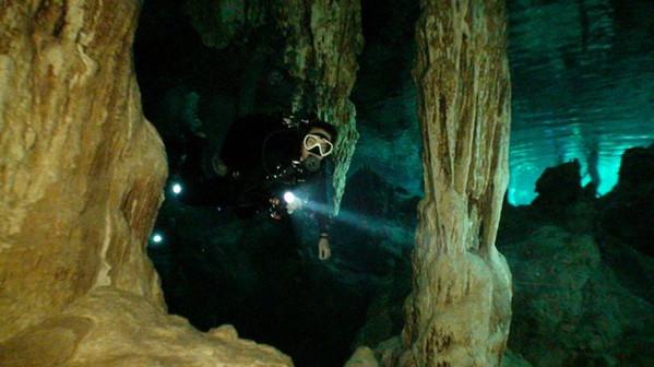 Scuba diving between stalactatites in Dos Ojos cenote, in the Riviera Maya between Playa del Carmen and Tulum.