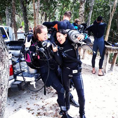Scuba diving women cenote diving and having a lot of fun in Mexico near Playa del Carmen