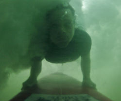 richard lyons doing a duckdive with custom board in tamarindo costa rica surfing