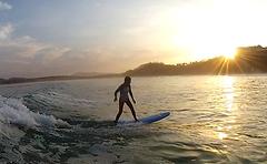 Catherine surfing into the sunrise  advanced surf lesson in tamarindo costa rica