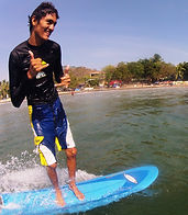 Alex surfing pico pequeno on soft top surfboard in tamarindo costa rica giving the shaka sign