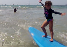 kids surf lesson girl surfing in front of pedro's surf shop