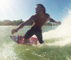 pedro cruz doing a bottom turn on red mini Custom monkey wrench surfboard from pedro's surf shop and school in tamarindo costa rica