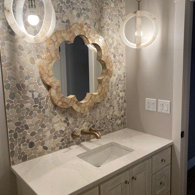 Pebble Stone backsplash- Wall Faucet- Gold Bathroom FIxtures.jpg