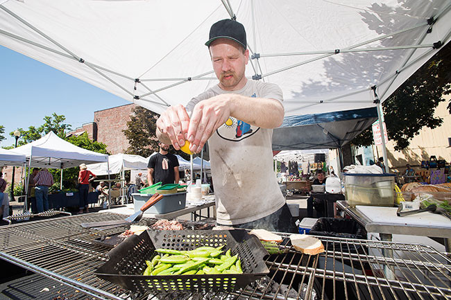 Owner/Cook Kyle Chriestenson from The Diner prepares a few sandwiches for patrons at season's first McMinnville Farmer's Market. // by Marcus Larson
