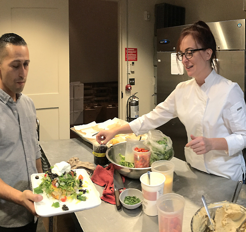As Brent works at mixing ingredients for the salmon course, Norma hands off a salad dish to Dayson Tiogangco while Jaclyn Easton looks on.