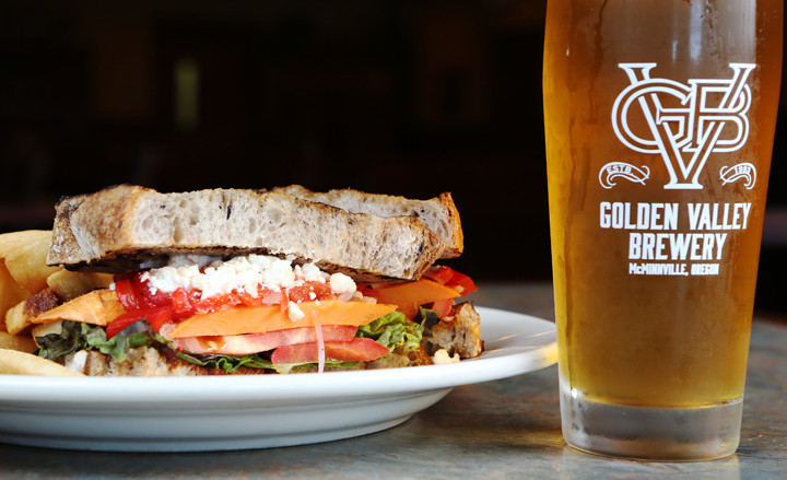 Golden Valley Brewery Beaverton Blonde with a Northwest veggie sandwich: roasted sweet potatoes and red peppers, red onions, tomato, feta, romesco sauce, red leaf lettuce on Kalamata bread. // Rockne Roll