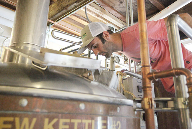 Brewer Jake Miller checks in on brew fermenting with pounds of Douglass fir bark chips in the mix.