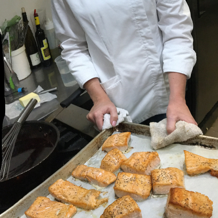 Norma and the evening's main course, the salmon, await the next step in the process, plating.