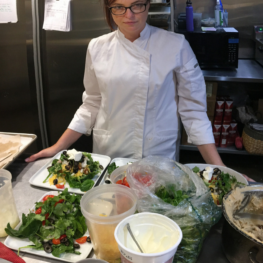 With the ingredients in front of her, Norma begins the process of putting the salad together. The greens will be mated with the Navajo Flatbread.