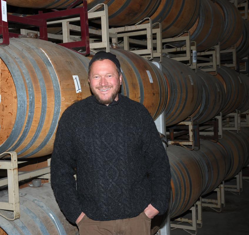 Tad Seestedt is all smiles with barrels of spirits awaiting in the background awaiting bottling when the aging peaks.