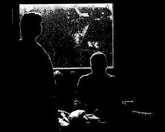 Two figures silhouetted at a window
