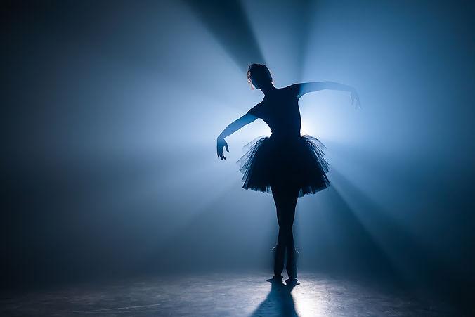 Ballerina in black tutu dress dancing on