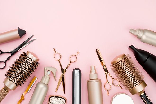 Various hair dresser tools on pink backg