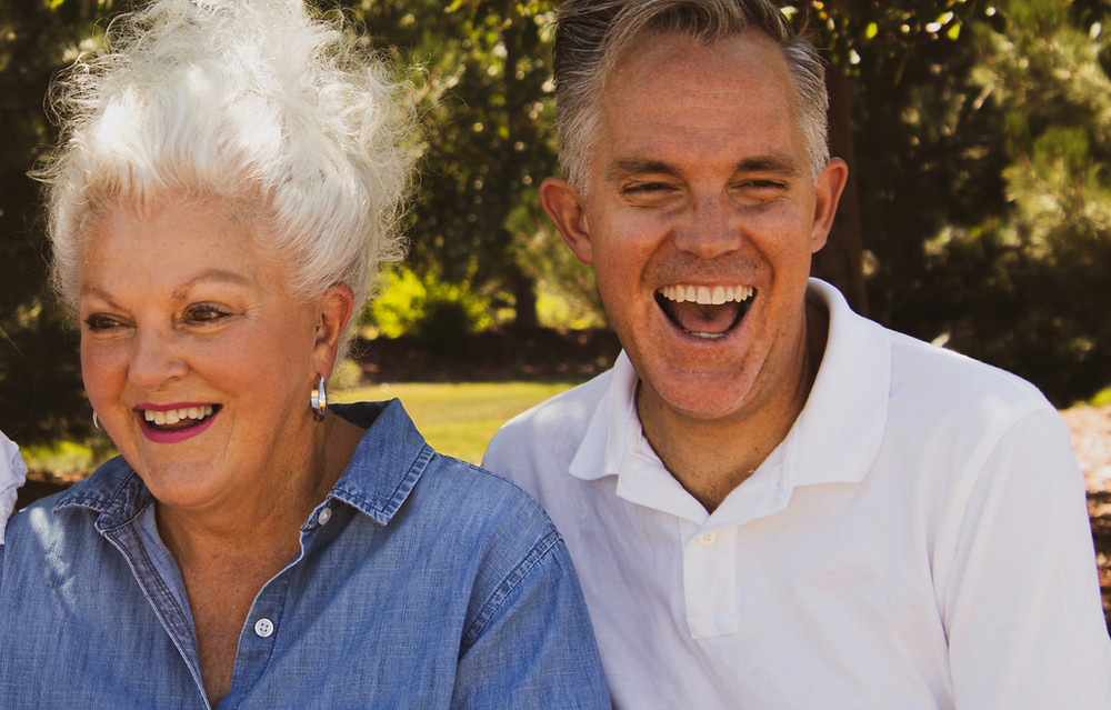 A mature couple enjoying an outrageous laugh while in the park