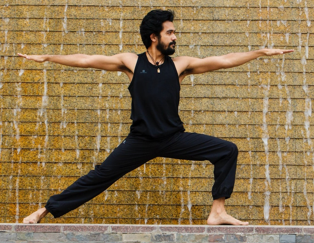 man performing the yoga pose in front of a water wall