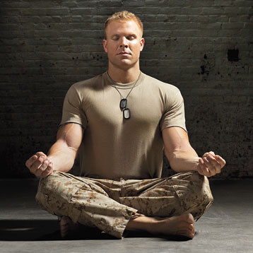 A US military soldier postured on the floor to practice meditation to help with his PTSD symptoms