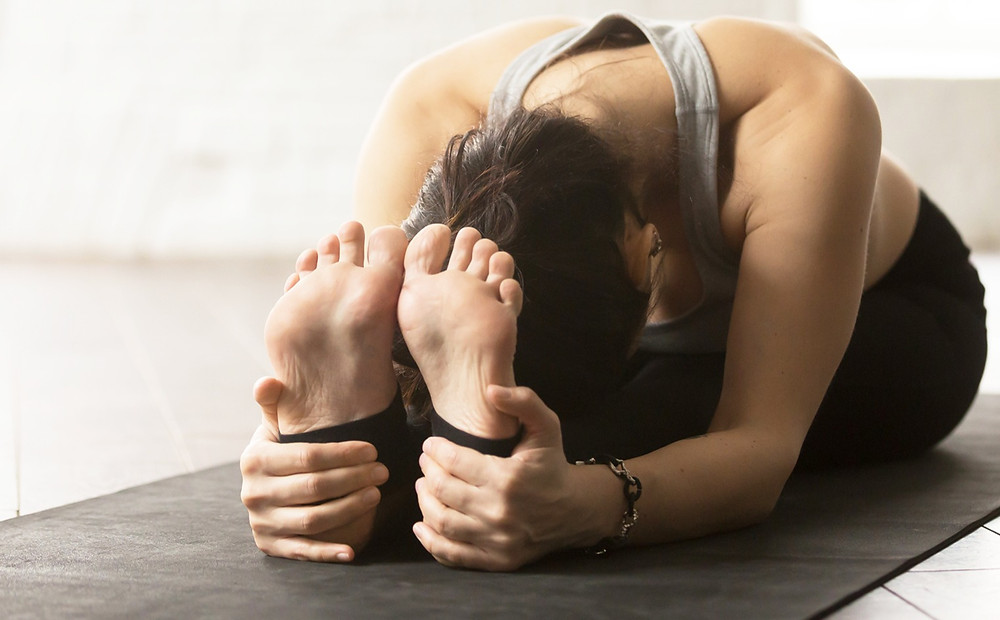 Woman grabbing her heels in the seated forward bend pose