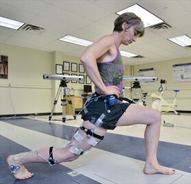 Woman in research test lab for osteoarthritis practicing lunges while wearing strapped sensors on her body