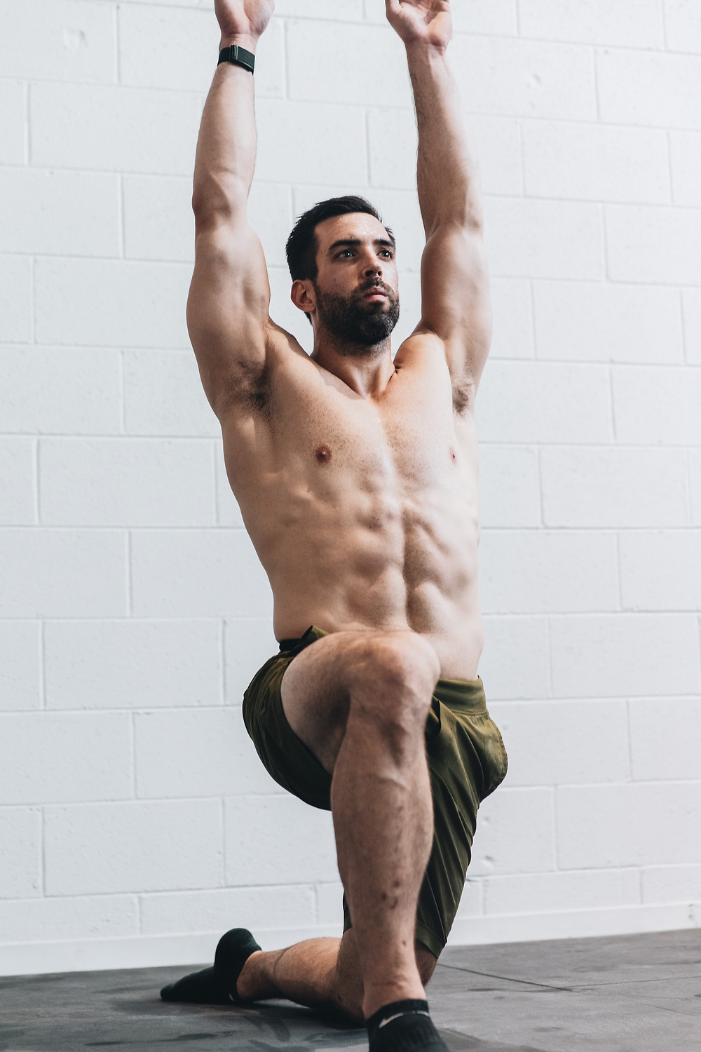 A muscular man on his knee holding the Runner's Lunge yoga pose for 30 seconds.