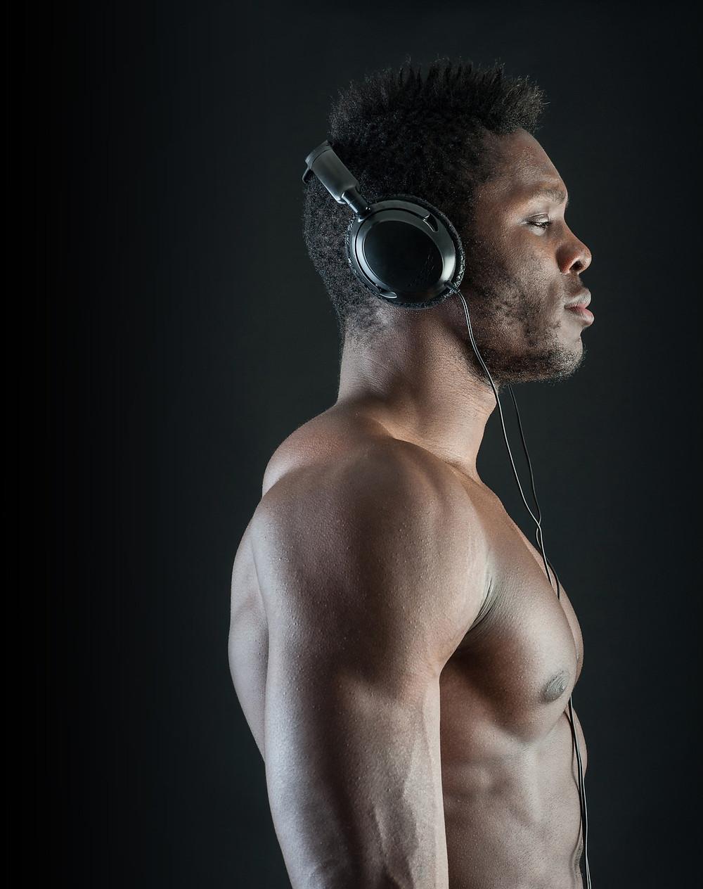 A muscular shirtless black man listening to a workout meditation on head set