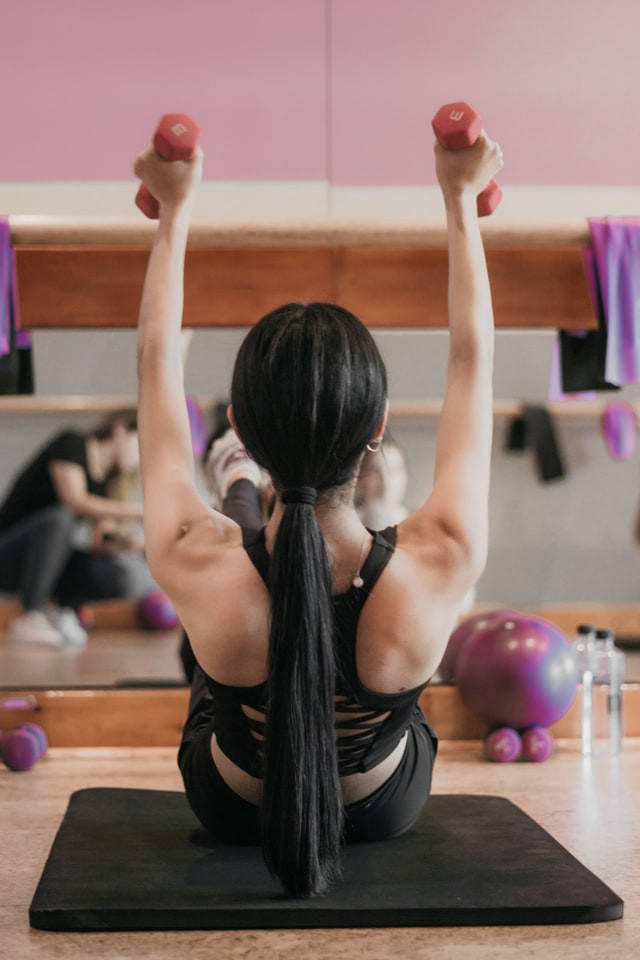 Woman performing arm lift pose with 2 lbs. weights