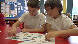 Boys engaged in playing a Languag Magnet board game