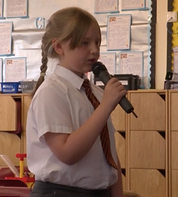 pupil learning to speak to an audience in French