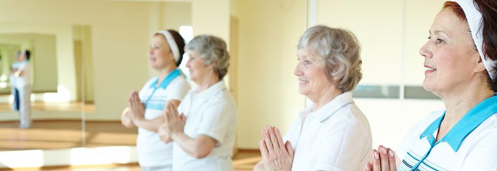 On voit des personnes du 3° age effectuer une séance de sport adapté dans une salle de gym équipée d'un mirroir
