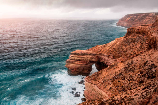 Lonely girl sitting on rock formation at Kalbarri National Park, Western Australia