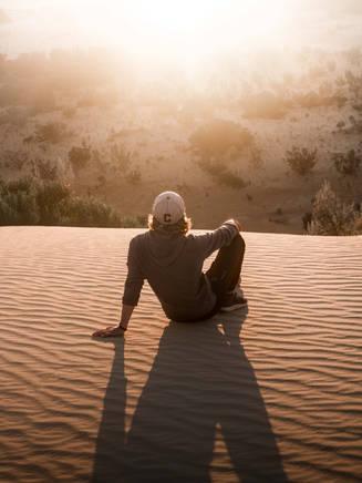 Young man watching sunset in pinnacle desert, Nambung National Park, Western Australia